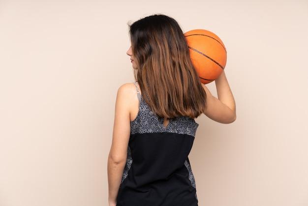Joven jugando baloncesto sobre pared aislada