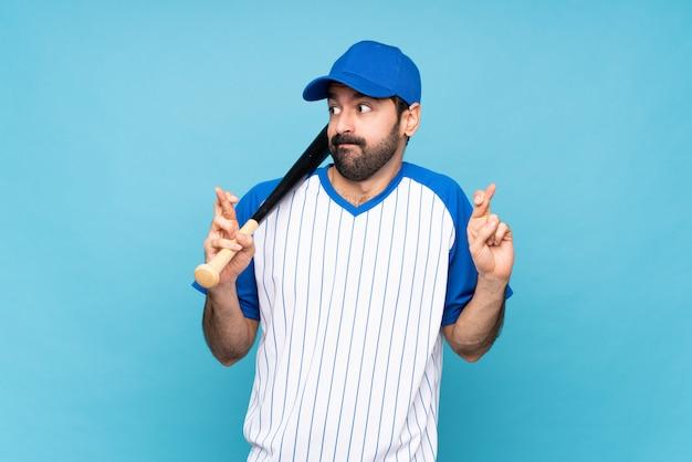 Joven jugando béisbol sobre azul aislado con dedos cruzando y deseando lo mejor