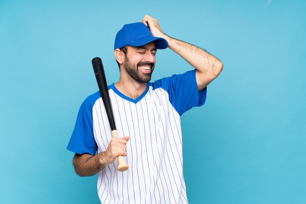 Joven jugando béisbol sobre azul aislado se ha dado cuenta de algo y tiene la intención de la solución