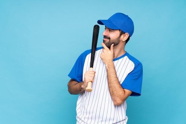 Joven jugando béisbol sobre azul aislado mirando hacia el lado