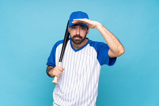 Joven jugando béisbol sobre azul aislado mirando lejos con la mano para mirar algo