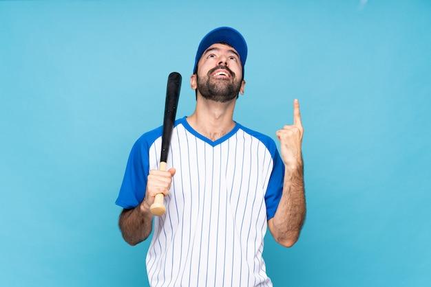Joven jugando béisbol sobre pared azul aislado apuntando hacia arriba y sorprendido