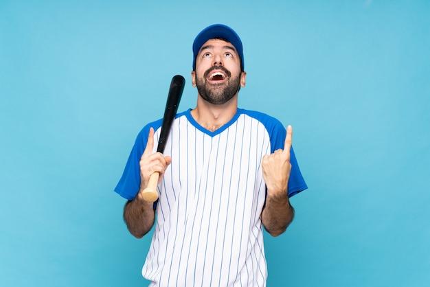 Joven jugando béisbol sobre pared azul aislado sorprendido y apuntando hacia arriba