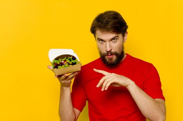 Joven con una jugosa hamburguesa en sus manos, un hombre comiendo una hamburguesa