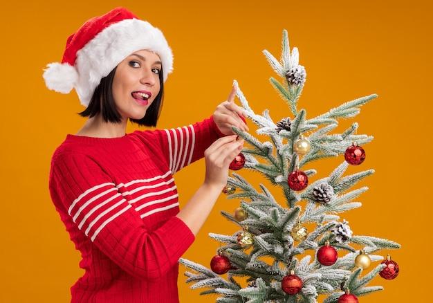 Joven juguetona con gorro de papá noel de pie en la vista de perfil cerca del árbol de navidad decorándolo con adornos navideños mirando a cámara mostrando lengua aislada sobre fondo naranja