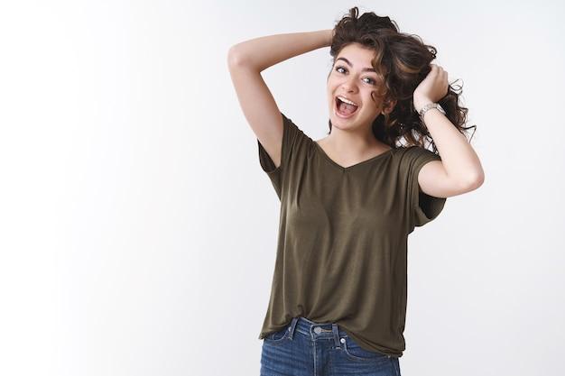 Joven juguetona niña caucásica salvaje jugando cabello tocando hebras gritando canto divirtiéndose expresan positividad alegre estado de ánimo, de pie fondo blanco afortunado emocionado tener día perfecto