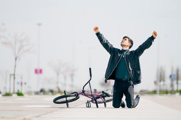 Joven junto a su bicicleta levantando los puños de rodillas