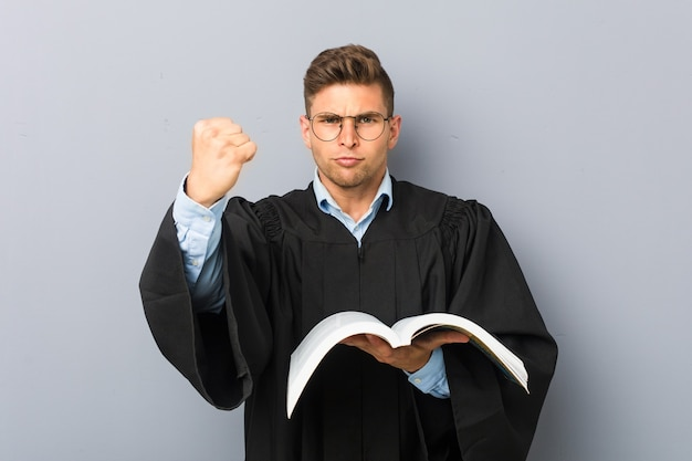 Joven jurista sosteniendo un libro mostrando el puño a la cámara, expresión facial agresiva.