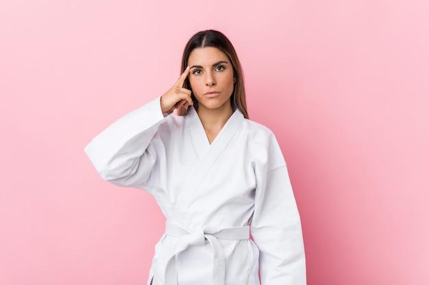 Joven karate mujer apuntando el templo con el dedo, pensando, centrado en una tarea.