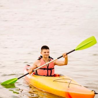 Joven kayakista masculino kayak en el lago