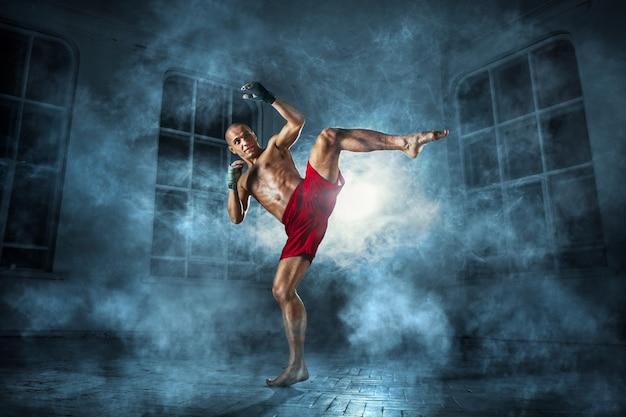 El joven kickboxing en humo azul
