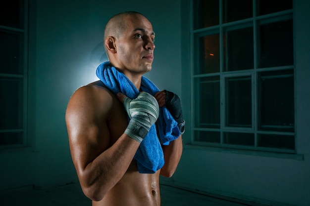 El joven kickboxing en pared negra