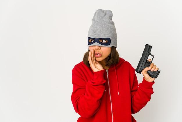 Joven ladrón mujer hispana con una máscara está diciendo una noticia secreta de frenado en caliente y mirando a un lado