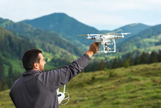 Joven lanza un quadrocopter en el cielo sobre la naturaleza en las montañas