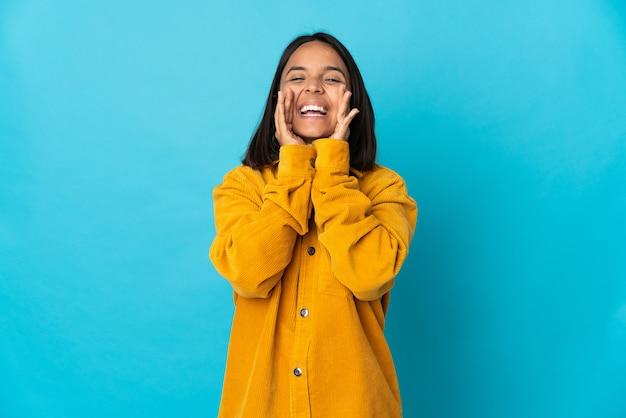 Joven latina aislada en la pared azul gritando y anunciando algo