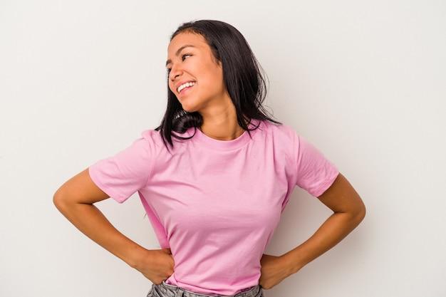 Joven latina aislada sobre fondo blanco se ríe alegremente y se divierte manteniendo las manos sobre el estómago.