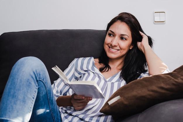 Joven latina disfrutando de un buen libro sentado en el sofá en casa.