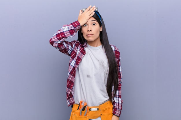 Joven latina en pánico por una fecha límite olvidada, sintiéndose estresada, teniendo que ocultar un desastre o error