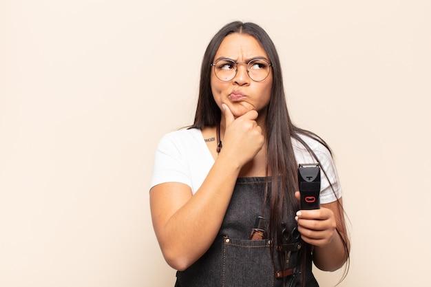 Joven latina pensando, sintiéndose dudoso y confundido, con diferentes opciones, preguntándose qué decisión tomar