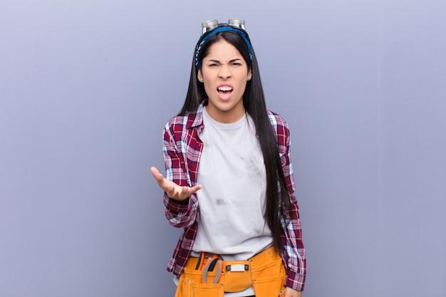 Joven latina que parece enojada, molesta y frustrada gritando wtf o qué pasa contigo