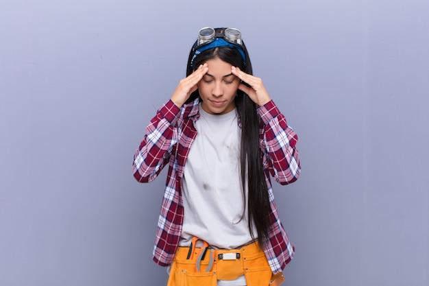 Joven latina que parece estresada y frustrada, trabajando bajo presión con dolor de cabeza