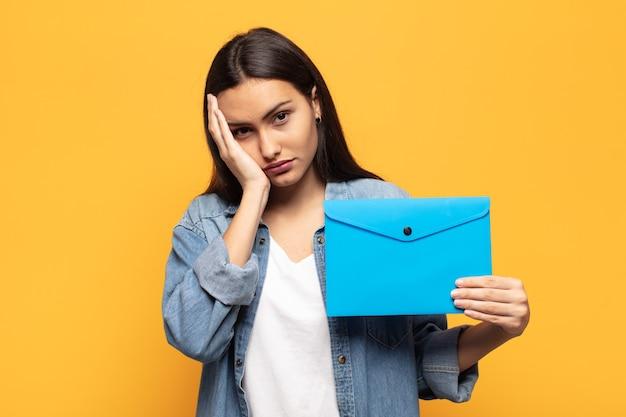 Joven latina que se siente aburrida, frustrada y con sueño después de una tarea tediosa, aburrida y tediosa, sosteniendo la cara con la mano