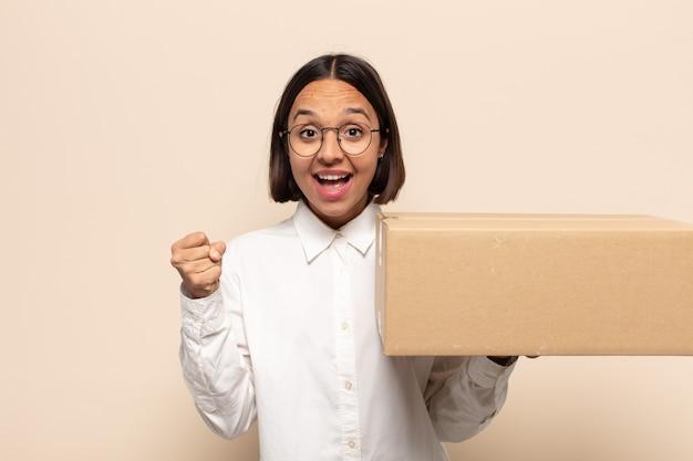 Joven latina que se siente sorprendida, emocionada y feliz, riendo y celebrando el éxito, diciendo ¡guau!