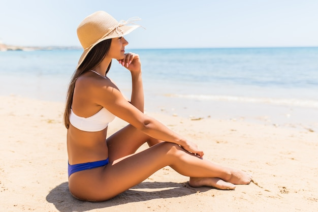 Joven latina con sombrero de paja sentado en la playa del mar