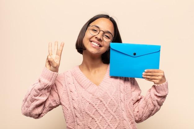 Joven latina sonriendo y mirando amistosamente, mostrando el número tres o tercero con la mano hacia adelante, contando hacia atrás