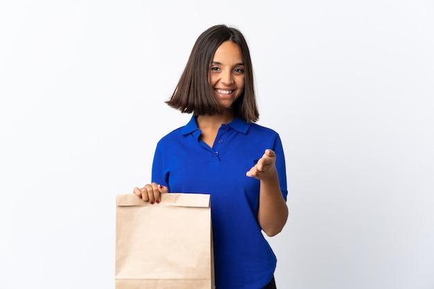 Joven latina sosteniendo una bolsa de compras aislada
