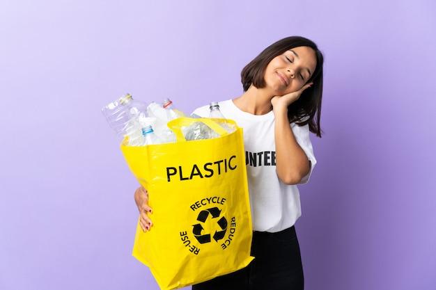 Joven latina sosteniendo una bolsa de reciclaje llena de papel para reciclar aislado en púrpura haciendo gesto de sueño en expresión dorable