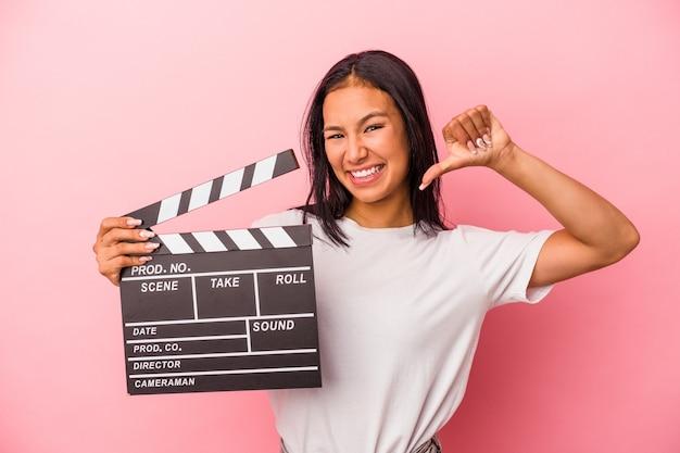 Joven latina sosteniendo claqueta aislada sobre fondo rosa se siente orgullosa y segura de sí misma, ejemplo a seguir.