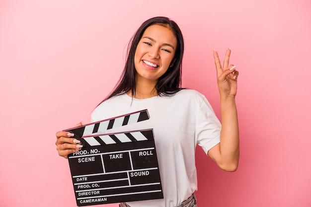 Joven latina sosteniendo claqueta aislado sobre fondo rosa alegre y despreocupado mostrando un símbolo de paz con los dedos.