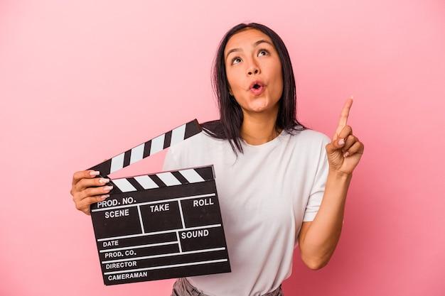 Joven latina sosteniendo claqueta aislado sobre fondo rosa apuntando al revés con la boca abierta.