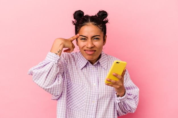 Joven latina sosteniendo un teléfono móvil aislado sobre fondo rosa mostrando un gesto de decepción con el dedo índice.