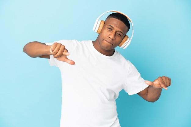 Joven latino aislado en la pared azul escuchando música y bailando
