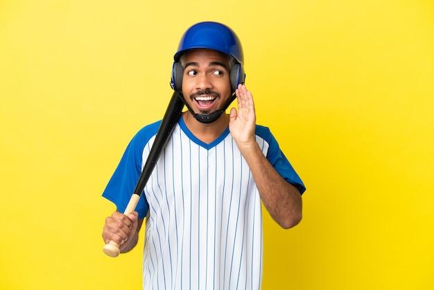 Joven latino colombiano jugando béisbol aislado sobre fondo amarillo escuchando algo poniendo la mano en la oreja