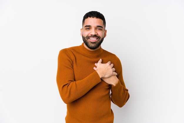 El joven latino contra un blanco aislado tiene una expresión amistosa, presionando la palma contra el pecho. concepto de amor