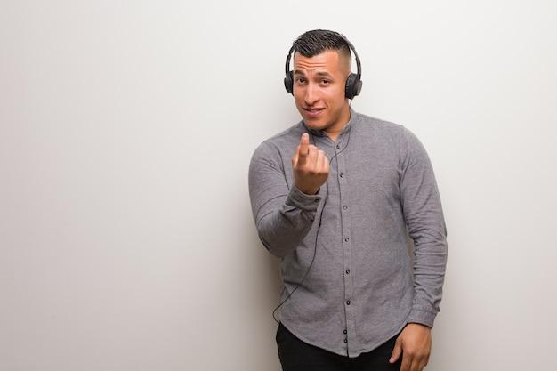 Joven latino escuchando música invitando a venir