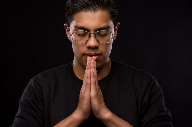 Joven latino orando