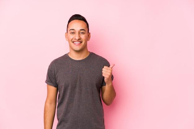 Joven latino posando en rosa sonriendo y levantando el pulgar hacia arriba