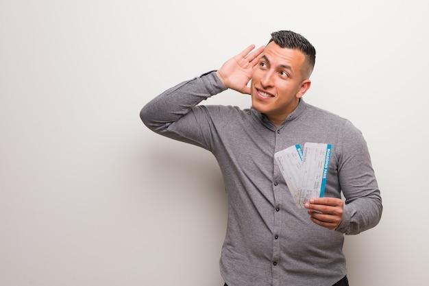 Joven latino sosteniendo un billete de avión intenta escuchar un chisme