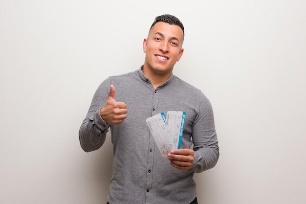 Joven latino sosteniendo un billete de avión sonriendo y levantando el pulgar