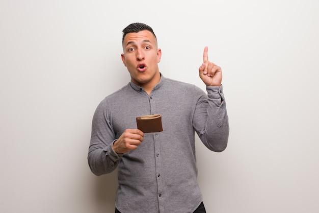 Joven latino sosteniendo una billetera con una gran idea, de creatividad