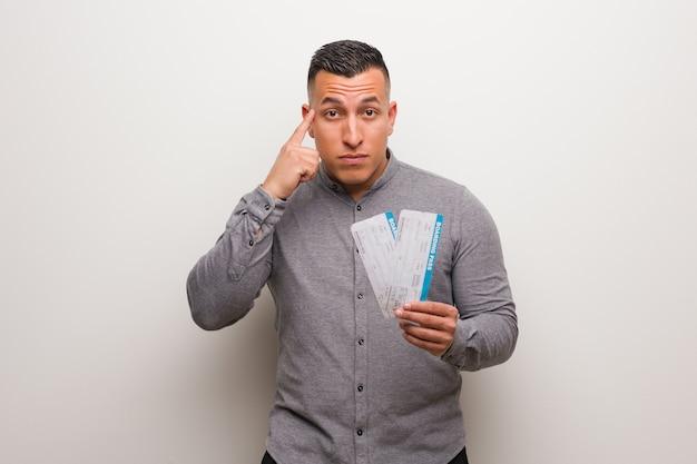 Joven latino sosteniendo un boleto aéreo pensando en una idea