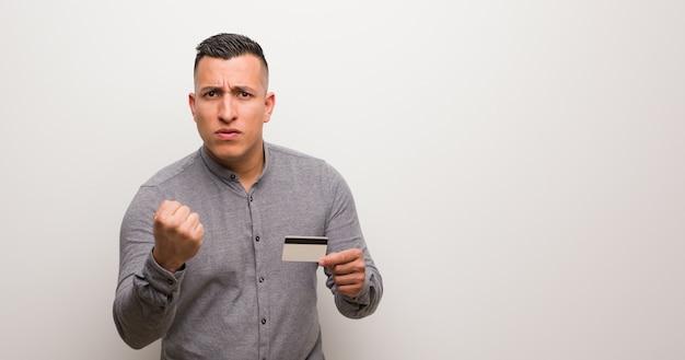 Joven latino sosteniendo una tarjeta de crédito mostrando el puño al frente, expresión enojada