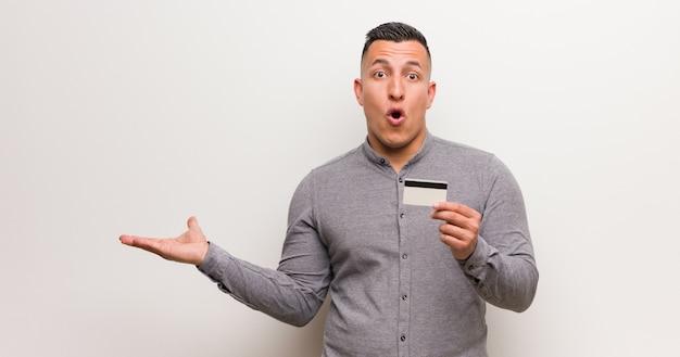 Joven latino sosteniendo una tarjeta de crédito sosteniendo algo en la mano de la palma