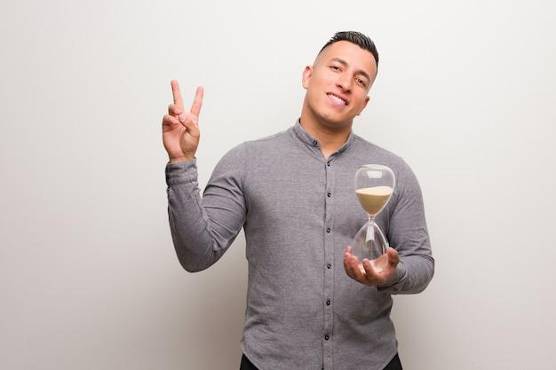 Joven latino sosteniendo un temporizador de arena mostrando el número dos