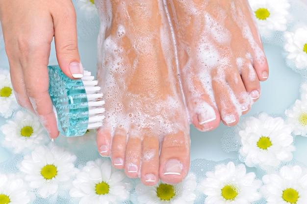 La joven lava y limpia las hermosas piernas bien arregladas con agua mediante un cepillo de limpieza.