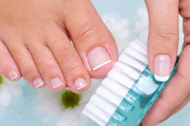 La joven se lava y limpia las uñas de los pies en agua con un cepillo de limpieza.